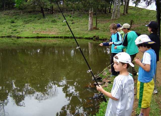 Group of boys fishing in pond hats tee shirts