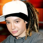 young boy in hat with dreads and piecring