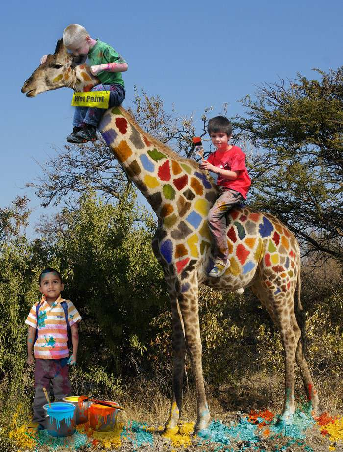 Boys painting a giraffe