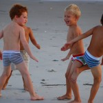 3 boys in underware play at beach