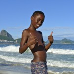 Young black boy gives thumbs up on the beach