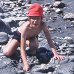 boy plays with rocks at beach