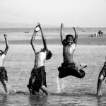 Group of boys jump at the beach