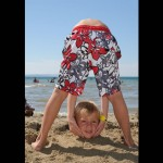 boy picks up head at beach