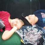 2 boys asleep in car