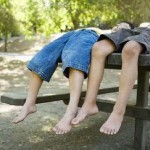 Boys sleeping on park bench