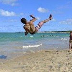 boy doing flip at beach