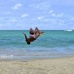 Boy does back flip at beach