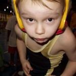 Young boy wearing wrestling headgear