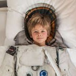 Boy Sleeping Under Astronaut Comforter