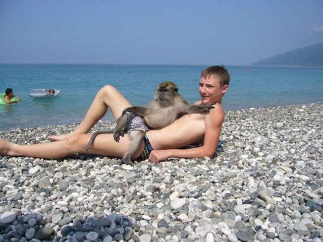 Boy wearing Speedos with pet monkey?